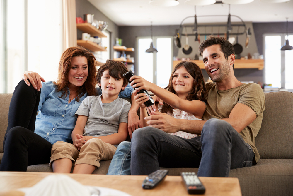 A happy family of four enjoying television.